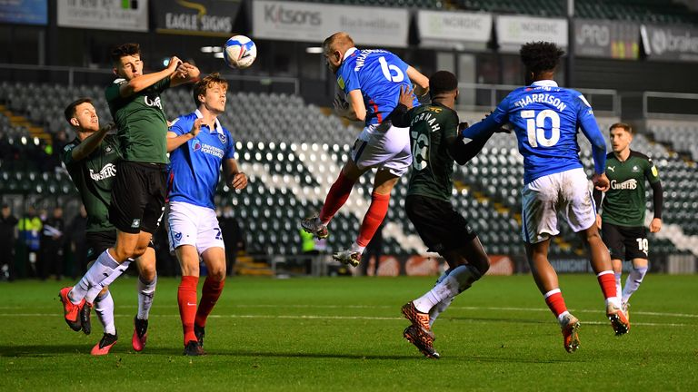 PLYMOUTH, ENGLAND - NOVEMBER 16: Kelland Watts of Plymouth Argyle (2L) blocks a header from Jack Whatmough of Portsmouth with his arms resulting in a penalty during the Sky Bet League One match between Plymouth Argyle and Portsmouth at Home Park on November 16, 2020 in Plymouth, England.