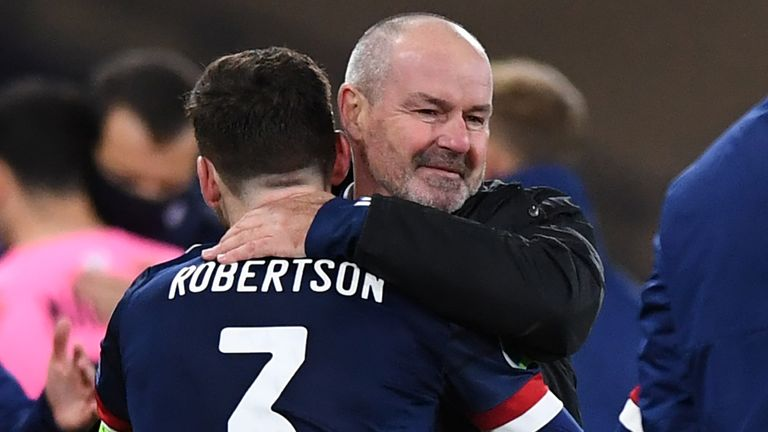 Steve Clarke (centre right) embraces Scotland's defender Andrew Robertson (centre left) on the pitch after Scotland win the penalty shoot-out during the Euro 2020 playoff semi-final football match between Scotland and Israel at Hampden Park, Glasgow on October 8, 2020. - Scotland won the penalty shoot-out 5-3 after the game finished 0-0 after extra time