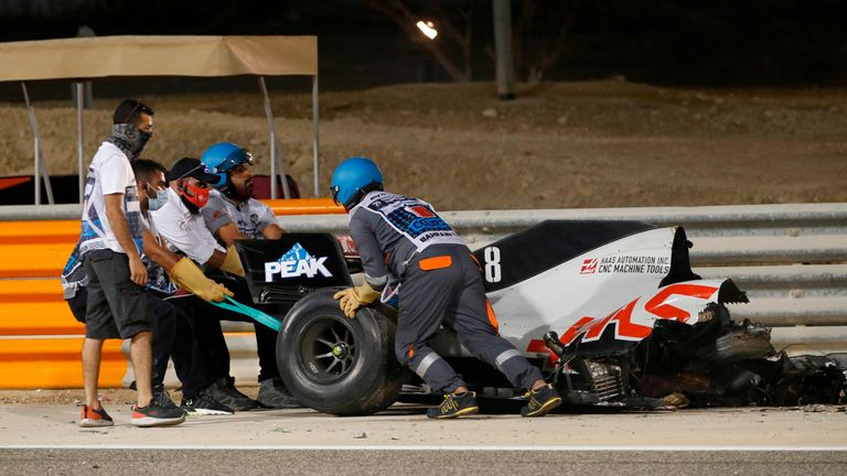 Stewards recover a section of Romain Grosjean's car following a crash during the Bahrain GP