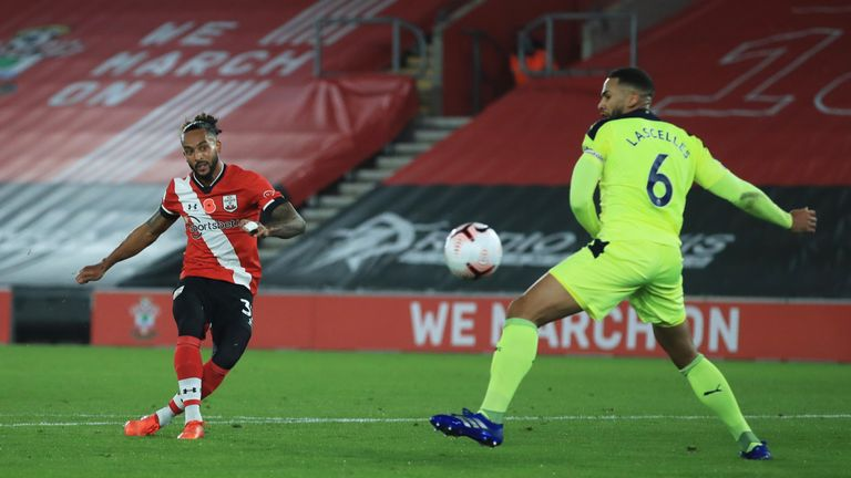 Theo Walcott curls his effort wide of the post as Saints stream forward
