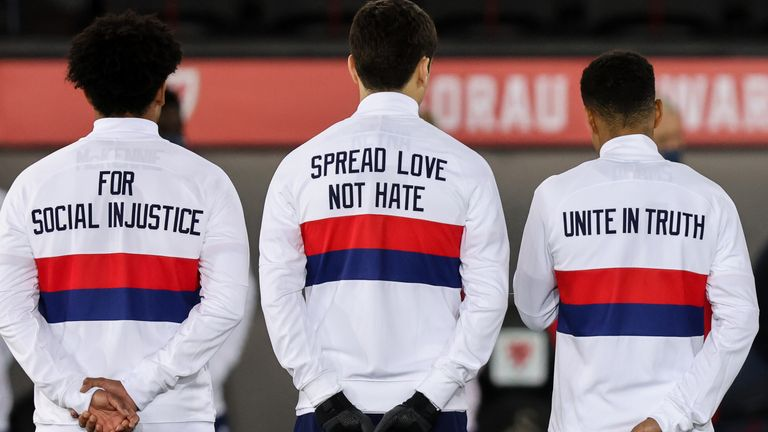 USA players lined up for the national anthems with anti-racism messages on the back of their training tops