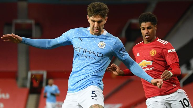 John Stones and Marcus Rashford in action during the Manchester derby