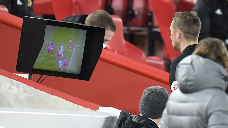 Referee Craig Pawson checks the pitchside monitor before overturning his decision to award a penalty to Wolves