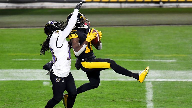 Diontae Johnson of the Pittsburgh Steelers makes a reception over Davontae Harris of the Baltimore Ravens