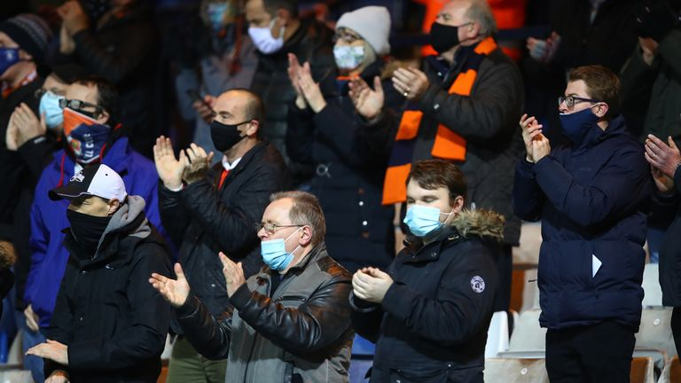 Fans of Luton Town applaud from their socially distanced seating whilst wearing a face mask ahead of the Sky Bet Championship match between Luton Town and Norwich City at Kenilworth Road