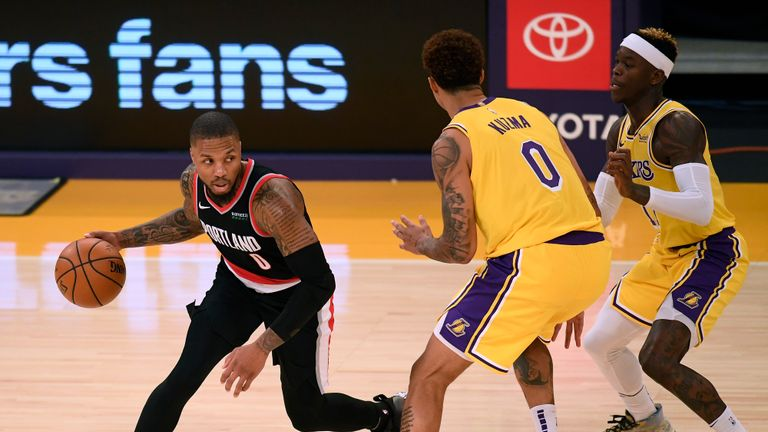 Damian Lillard #0 of the Portland Trail Blazers dribbles away from a double team by Kyle Kuzma #0 and Dennis Schroder #17 of the Los Angeles Lakers during a 115-107 Trail Blazer win at Staples Center on December 28, 2020 in Los Angeles, California.
