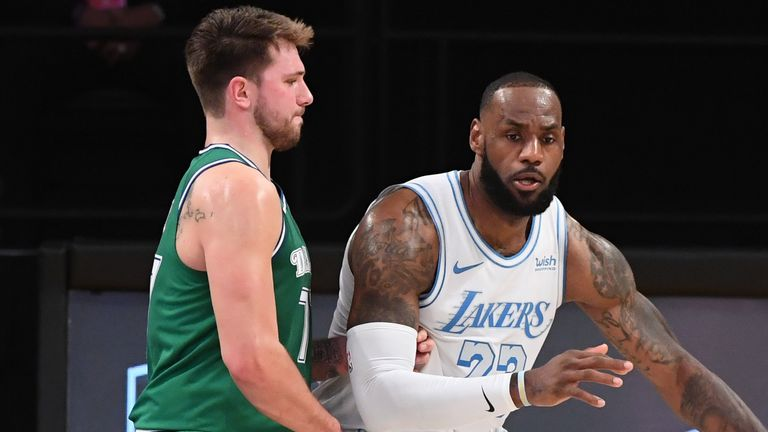 LeBron James #23 of the Los Angeles Lakers handles the ball against Luka Doncic #77 of the Dallas Mavericks during the game on December 25, 2020