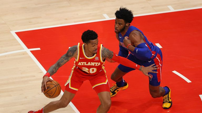 John Collins #20 of the Atlanta Hawks is defended by Saddiq Bey #41 of the Detroit Pistons during the first half at State Farm Arena on December 28, 2020 in Atlanta, Georgia.