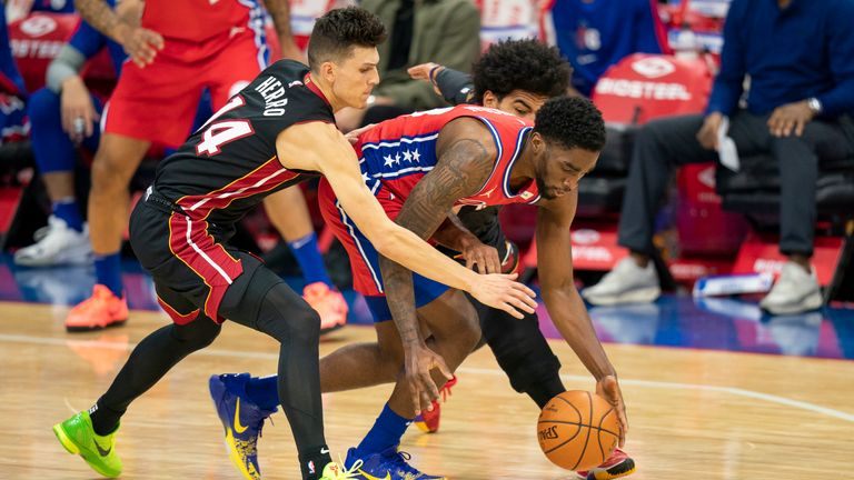 Philadelphia 76ers' Shake Milton reaches for the ball with Miami Heat's Tyler Herro and Gabe Vincent defending