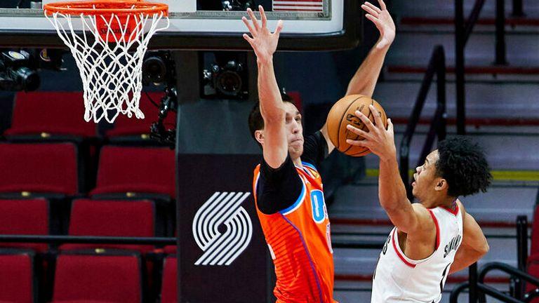 AP - Portland Trail Blazers guard Anfernee Simons, right, rises to dunk over Oklahoma City Thunder forward Aleksej Pokusevski