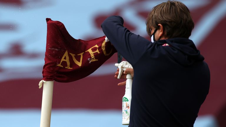 A member of staff disinfects a corner flag before the Premier League match at Villa Park, Birmingham.