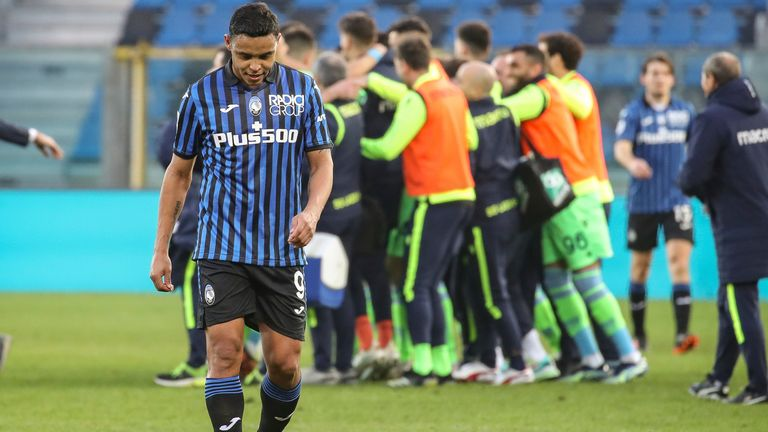 Atalanta's Luis Muriel leaves the field as Lazio players celebrate their victory