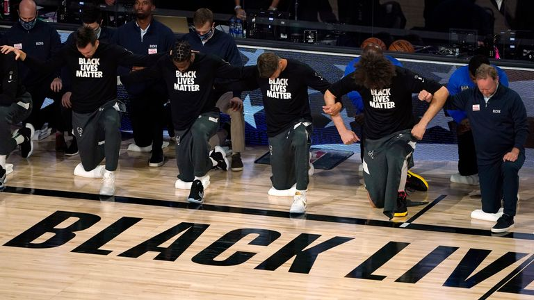 Milwaukee Bucks join arms as they kneel during the National Anthem before last summer's first round playoff game against the Orlando Magic - AP