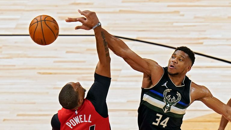 Milwaukee Bucks forward Giannis Antetokounmpo knocks a rebound away from Toronto Raptors guard Norman Powell