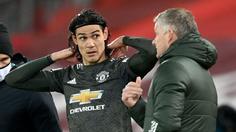 Manchester United's manager Ole Gunnar Solskjaer talks with Manchester United's Edinson Cavani during the English Premier League soccer match between Liverpool and Manchester United at Anfield Stadium, Liverpool, England, Sunday, Jan. 17, 2021. (Michael Regan/Pool via AP)