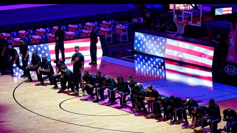 AP - The Boston Celtics team kneels during the playing of the National Anthem before the first half of an NBA basketball game against the Miami Heat