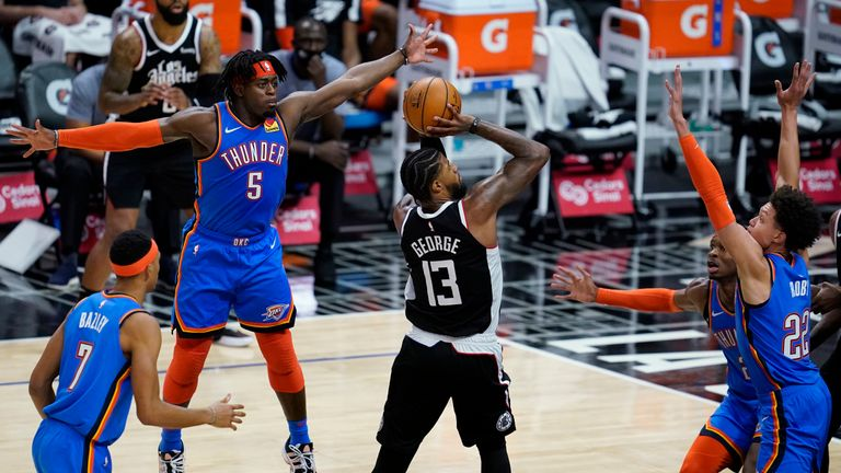 Los Angeles Clippers guard Paul George (13) shoots between Oklahoma City Thunder players, including forward Luguentz Dort (5), during the fourth quarter of an NBA basketball game Friday, Jan. 22, 2021, in Los Angeles. (AP Photo/Ashley Landis)