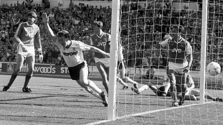 Luton Town's Danny Wilson (fourth l) celebrates scoring the equalizing goal to make the score 2-2, watched by teammates Mark Stein (l), Kingsley Black (sixth l, behind post) and Brian Stein (r, hidden), and Arsenal's Gus Caesar (second l), John Lukic (third l), Tony Adams (fifth l), Kenny Sansom (r) and Nigel Winterburn (r, hidden)
