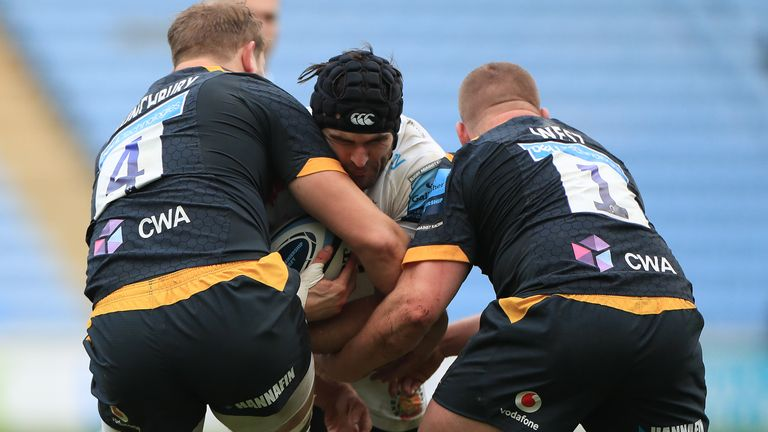Wasps' Tom West (right) and Joe Launchbury (left) tackle Exeter Chiefs' Don Armand