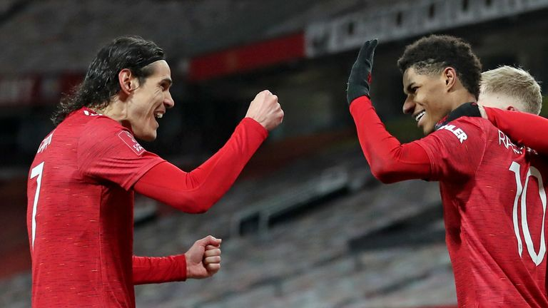 Manchester United...s Marcus Rashford, right, celebrates with Edinson Cavani after scoring his side...s second goal during the English FA Cup 4th round soccer match between Manchester United and Liverpool at Old Trafford in Manchester, England, Sunday, Jan. 24, 2021. (Martin Rickett/Pool via AP)..