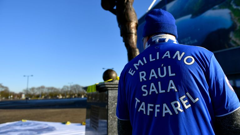 A fan wearing an Emliano Sala shirt looks at tributes at the Cardiff City Stadium