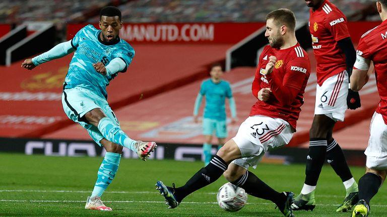 Georginio Wijnaldum has a shot on goal under pressure from Luke Shaw