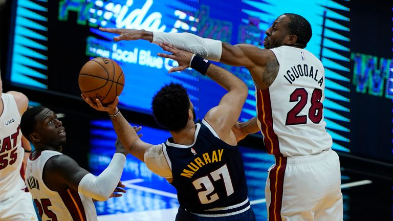 Miami Heat forward Andre Iguodala blocks a drive to the basket by Denver Nuggets guard Jamal Murray