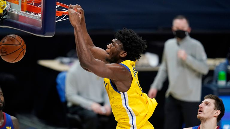 Golden State Warriors center James Wiseman hangs on the rim after dunking the ball for a basket against the Denver Nuggets
