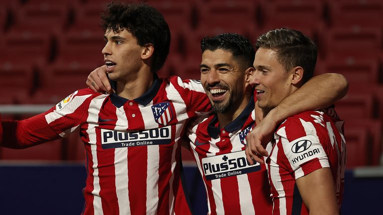 Luis Suarez of Atletico Madrid celebrates with his team-mates Joao Felix (L) and Marcos Llorente (R) after scoring against Valencia