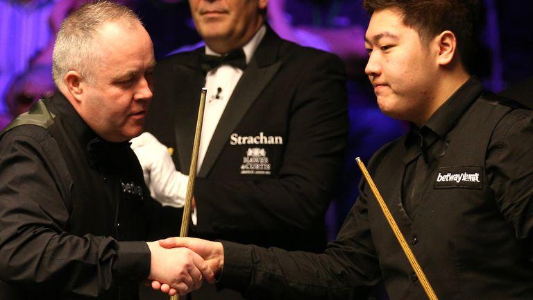 Higgins (left) shakes hands with Yan Bingtao