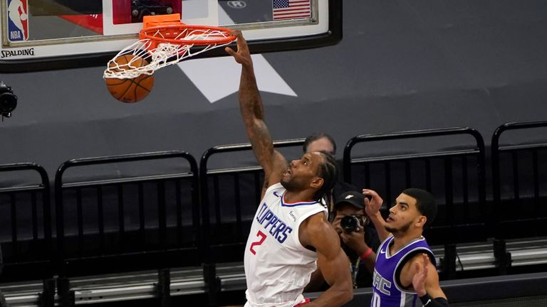 Los Angeles Clippers forward Kawhi Leonard dunks past Sacramento Kings guard Justin James, right, during the second half of an NBA basketball game
