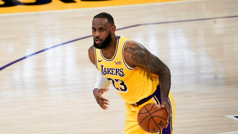 AP - Los Angeles Lakers' LeBron James dribbles the ball during the first half of an NBA basketball game against the Golden State Warriors