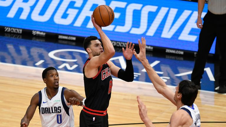 Chicago Bulls' Zach LaVine (8) goes up to shoot against Dallas Mavericks' Boban Marjanovic (51) and Josh Richardson (0) during the first half of an NBA basketball game Sunday, Jan. 3, 2021, in Chicago. (AP Photo/Paul Beaty)