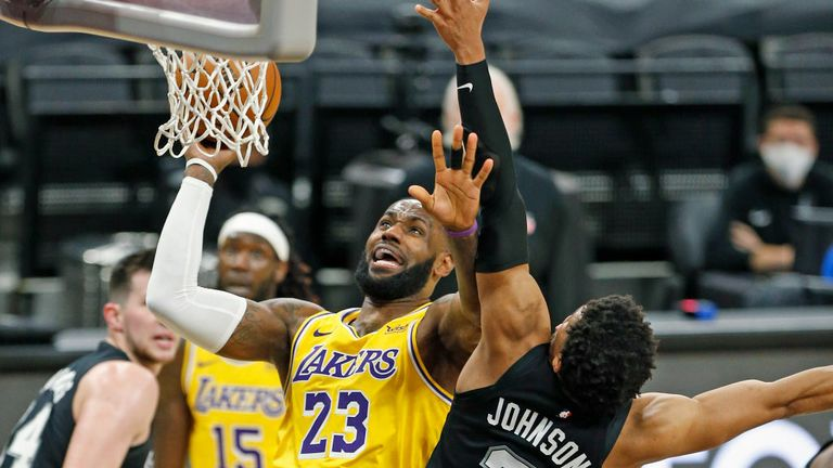 LeBron James #23 of the Los Angeles Lakers drives past Keldon Johnson #3 of the San Antonio Spurs #3 during second half action at AT&T Center