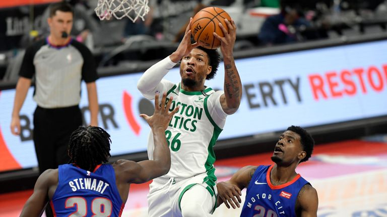 Boston Celtics guard Marcus Smart, center, drives between Detroit Pistons center Isaiah Stewart, left, and guard Josh Jackson during the first half of an NBA basketball game Sunday, Jan. 3, 2021, in Detroit. (AP Photo/Jose Juarez)