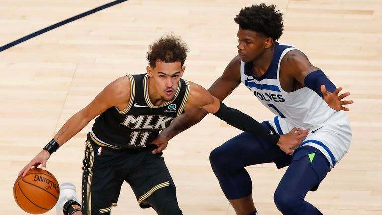 Atlanta Hawks guard Trae Young (11) battles Minnesota Timberwolves guard Anthony Edwards (1) in the second half of an NBA basketball game on Monday, Jan. 18, 2021, in Atlanta. (AP Photo/Todd Kirkland)