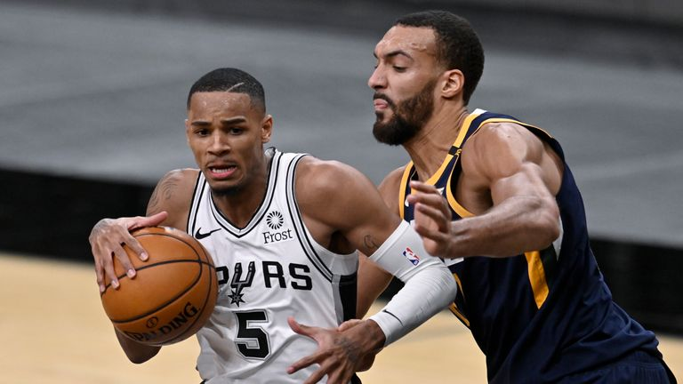 San Antonio Spurs' Dejounte Murray (5) drives around Utah Jazz's Rudy Gobert during the second half of an NBA basketball game, Sunday, Jan. 3, 2021, in San Antonio. (AP Photo/Darren Abate)
