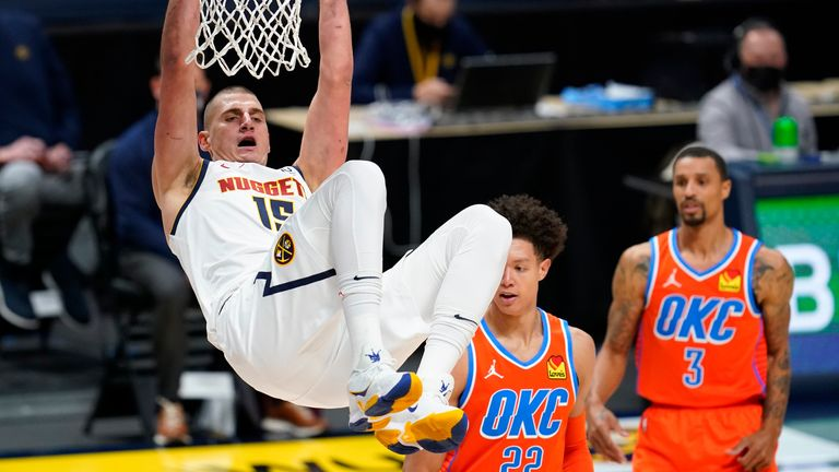 Denver Nuggets center Nikola Jokic, left, hangs from the rim after dunking the ball for a basket against Oklahoma City Thunder forward Isaiah Roby, center, and guard George Hill in the first half of an NBA basketball game Tuesday, Jan. 19, 2021, in Denver.