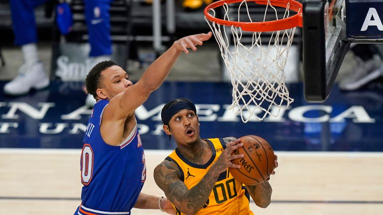 New York Knicks forward Kevin Knox II, left, defends as Utah Jazz guard Jordan Clarkson (00) goes to the basket in the second half during an NBA basketball game Tuesday, Jan. 26, 2021, in Salt Lake City. (AP Photo/Rick Bowmer)