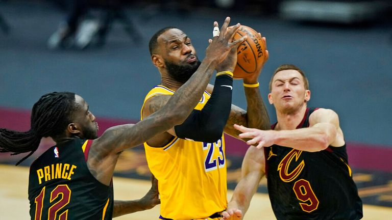AP - Los Angeles Lakers' LeBron James (23) drives to the basket between Cleveland Cavaliers' Taurean Prince (12) and Dylan Windler (9) in the second half