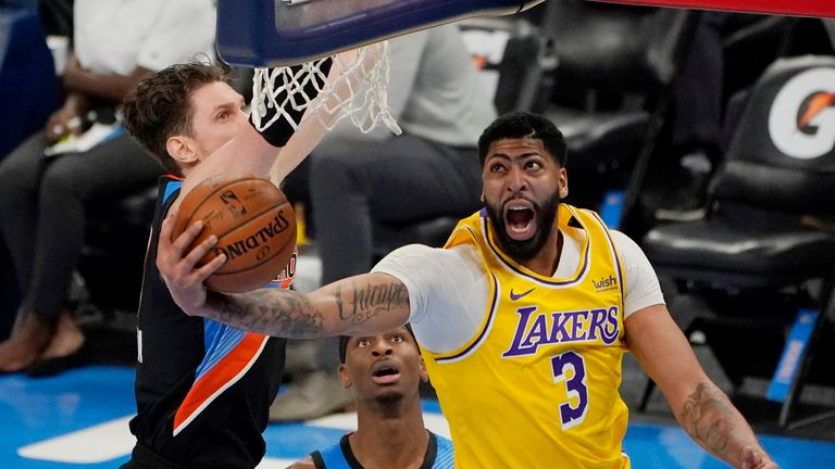 Los Angeles Lakers striker Anthony Davis (3) walks to the basket in front of Oklahoma City Thunder Center Mike Muscala, left and guard Shai Gilgeous-Alexander in the second half of an NBA basketball game on Wednesday, January 13, 2021 in Oklahoma City.  (AP Photo / Sue Ogrocki)