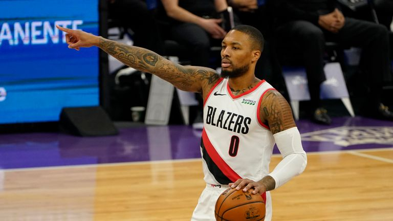 Portland Trail Blazers goaltender Damian Lillard waves to his teammates in the first quarter of the team's NBA basketball game against the Sacramento Kings in Sacramento, Calif. On Wednesday, Jan. 13, 2021. The Trail Blazers won 132 -126.  (AP Photo / Rich Pedroncelli)