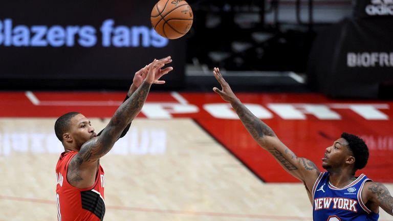 Portland Trail Blazers guard Damian Lillard, left, hits a shot over New York Knicks guard Elfrid Payton, right, during the second half of an NBA basketball game in Portland, Ore., Sunday, Jan. 24, 2021. The Blazers won 116-113.