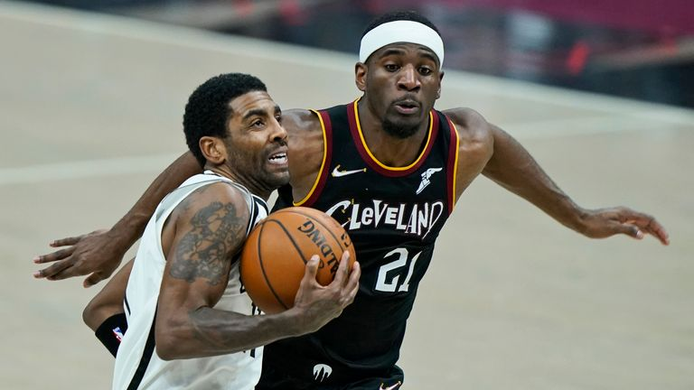 Brooklyn Nets' Kyrie Irving, front, drives to the basket against Cleveland Cavaliers' Damyean Dotson during the second half of an NBA basketball game, Wednesday, Jan. 20, 2021, in Cleveland. The Cavaliers won 147-135 in double-overtime.