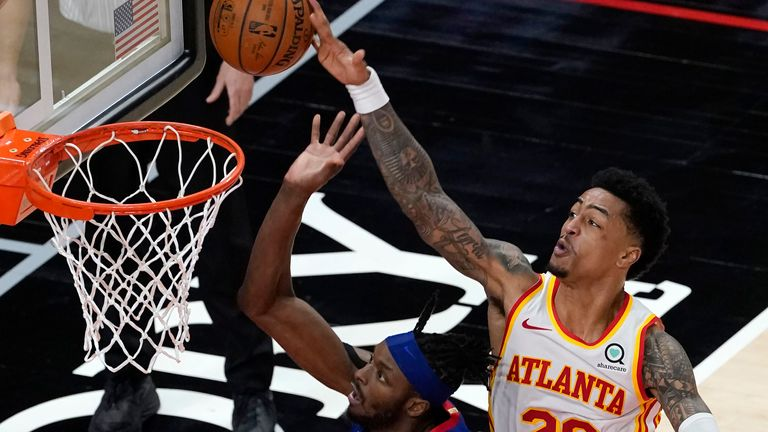 Detroit Pistons forward Jerami Grant (9) has his shot blocked by Atlanta Hawks forward John Collins (20) as he drives into Trae Young (11) at the end of the second half of an NBA basketball game Wednesday, Jan. 20, 2021, in Atlanta. The Hawks won 123-115 in overtime.