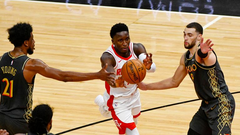 Houston Rockets guard Victor Oladipo, center, passes between Chicago Bulls forward Thaddeus Young, left, and guard Zach LaVine, right, during the second half of an NBA basketball game Monday, Jan. 18, 2021, in Chicago. (AP Photo/Matt Marton)