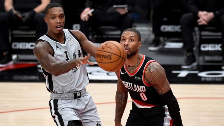 San Antonio Spurs guard Lonnie Walker IV, left, passes the ball on Portland Trail Blazers guard Damian Lillard, right, during the second half of an NBA basketball game in Portland, Ore., Monday, Jan. 18, 2021. (AP Photo/Steve Dykes)