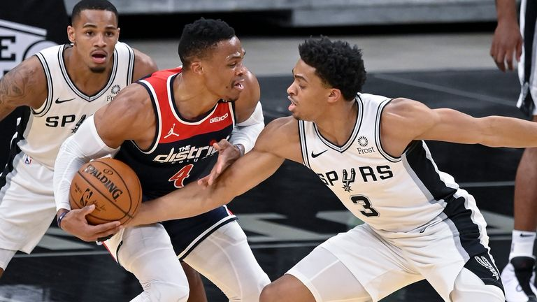 Washington Wizards' Russell Westbrook, center, fights to keep possession as he is defended by San Antonio Spurs' Keldon Johnson (3) and Dejounte Murray during the first half of an NBA basketball game, Sunday, Jan. 24, 2021, in San Antonio.