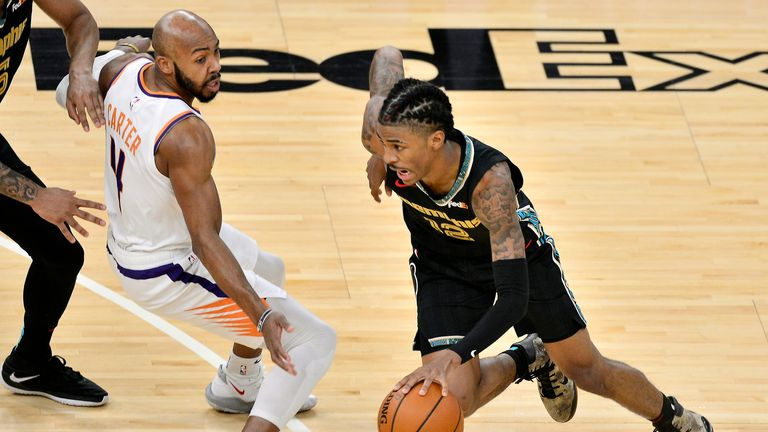 Memphis Grizzlies guard Ja Morant (12) drives against Phoenix Suns guard Jevon Carter (4) in the first half of an NBA basketball game Monday, Jan. 18, 2021, in Memphis, Tenn. (AP Photo/Brandon Dill)