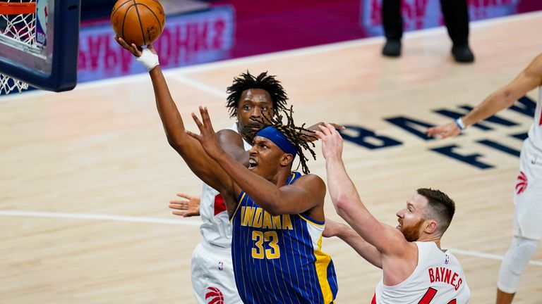 Indiana Pacers center Myles Turner (33) shoots between Toronto Raptors center Aron Baynes (46) and forward OG Anunoby (3) during the first half of an NBA basketball game in Indianapolis, Sunday, Jan. 24, 2021.